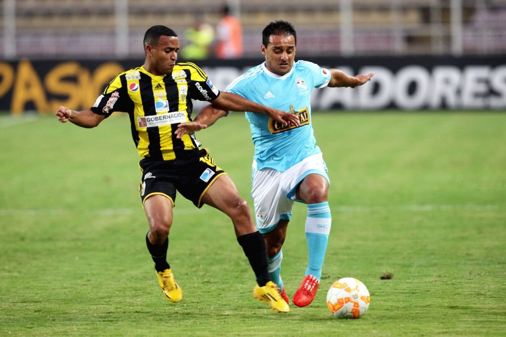 Deportivo Tachira's Yohandry Orozco (L) vies for the ball with Sporting Cristal's Cesar Emmanuel Pereyra (R) during the Group 8 match of the Libertadores Cup, held ...