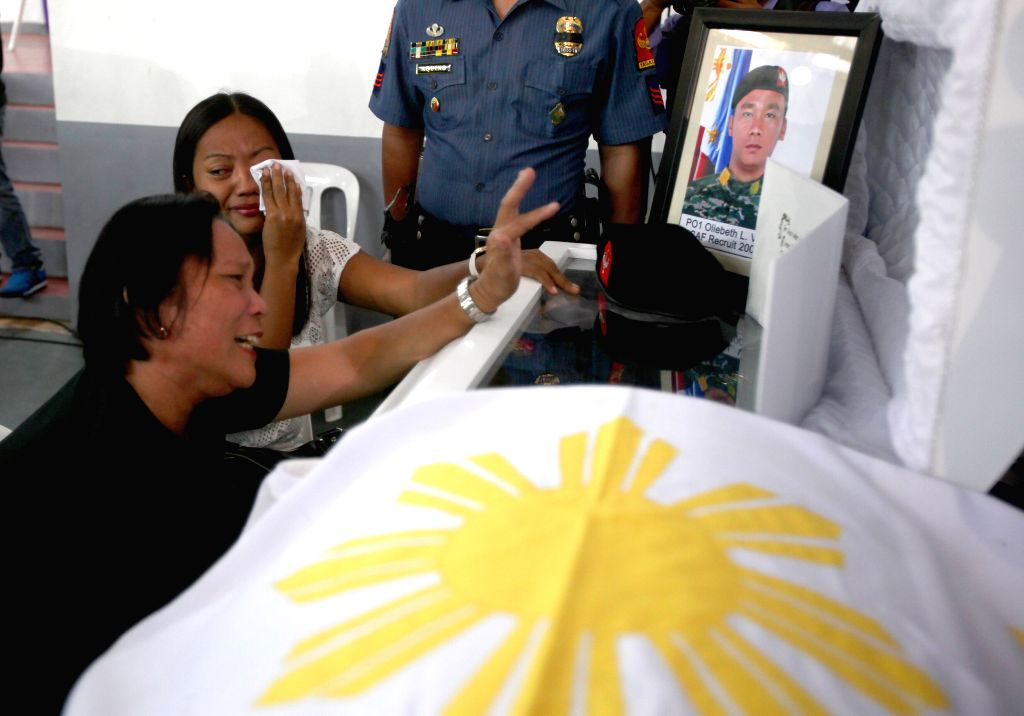 Family members weep on the casket of the slain members of the Philippine National Police Special Action Force (PNP-SAF) inside the Camp Bagong Diwa in Taguig ...