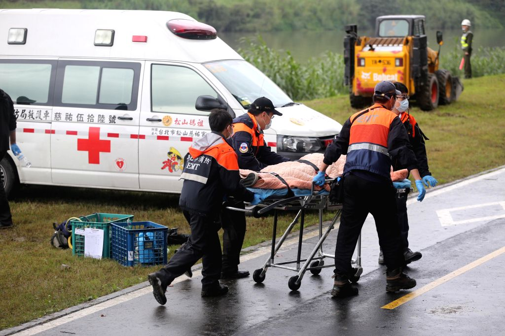 Rescuers transfer an injured passenger from a crashed plane in Taipei, southeast China's Taiwan, Feb. 4, 2015. A Taiwan TransAsia Airways plane crashed into a Taipei .