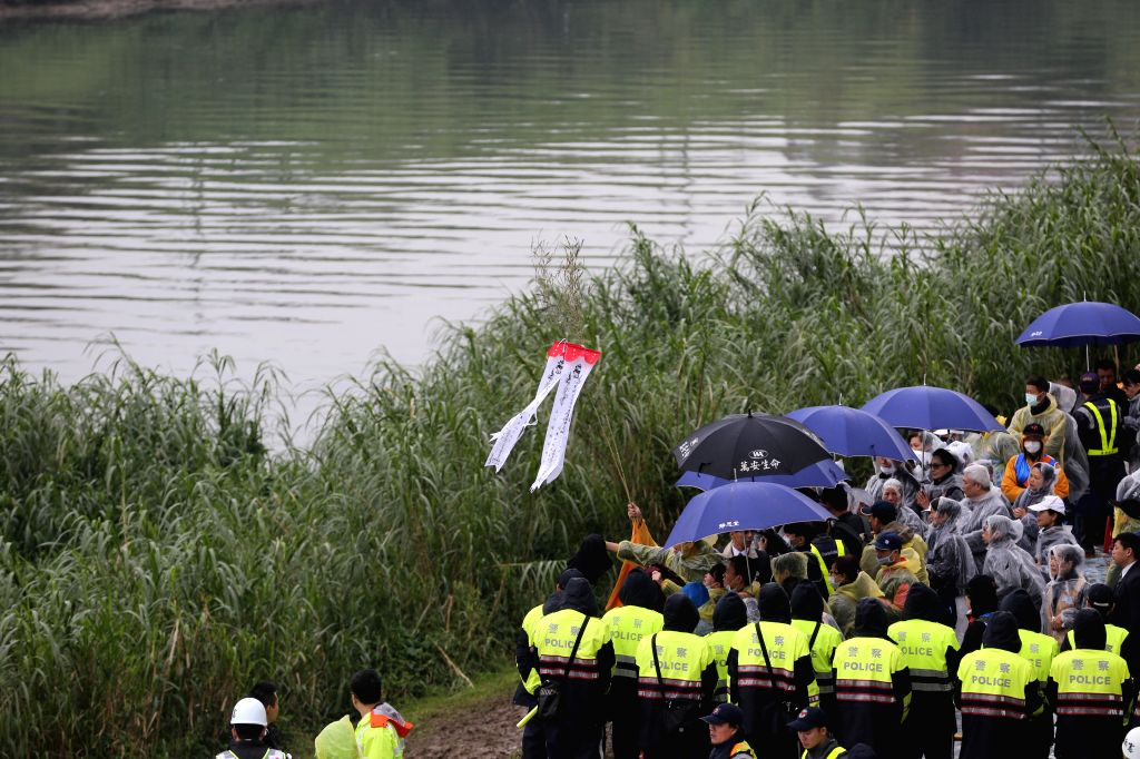 Relatives hold a memorial ceremony for plane crash victims on the bank of Keelung River in Taipei, southeast China's Taiwan, Feb. 6, 2015. Rescuers expanded the ...