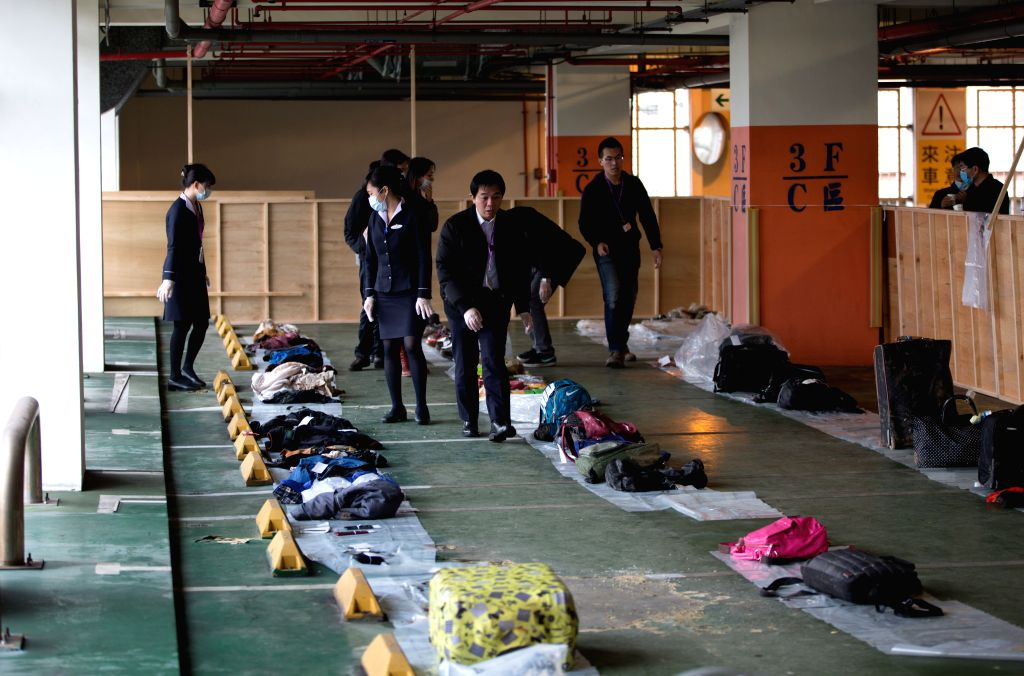 People claim the belongings of victims of the plane crash in Taipei, southeast China's Taiwan, Feb. 7, 2015. A plane of TransAsia Airways crashed in the Keelung ...