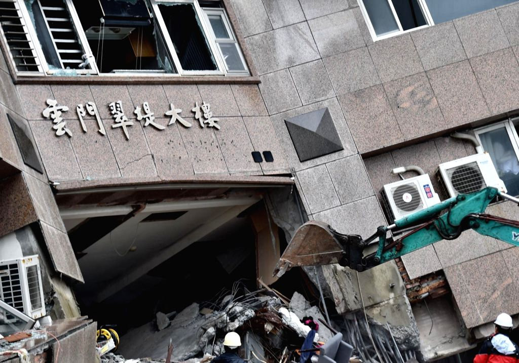 TAIPEI, Feb. 8, 2018 - An excavator is seen at the damaged Yun Men Tusi Ti building in Hualien, Taiwan, Feb. 8, 2018. Four tourists from the mainland had been confirmed dead as of Thursday morning ...
