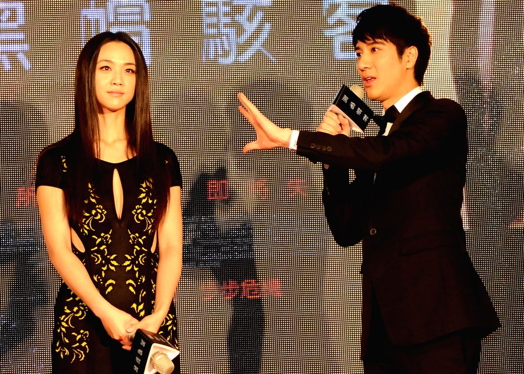 """Actress Tang Wei (L) and actor Leehom Wang react at the premiere of U.S. movie """"Blackhat"""" in Taipei, southeast China's Taiwan, Jan. 15, 2015."""