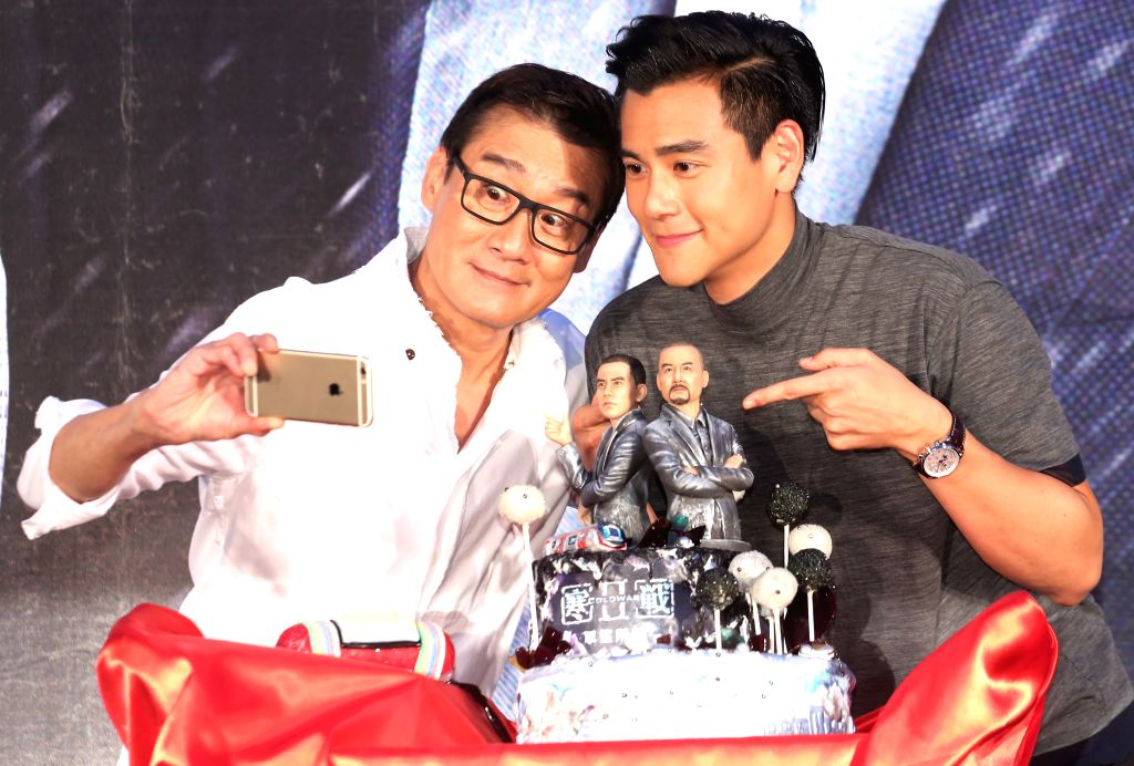 """TAIPEI, June 28, 2016 - Actor Tony Leung Ka Fai (L) and Eddie Peng take a selfie during the premiere of the movie """"Cold War 2"""" in Taipei, southeast China's Taiwan, June 28, 2016. The movie ... - Tony Leung K"""