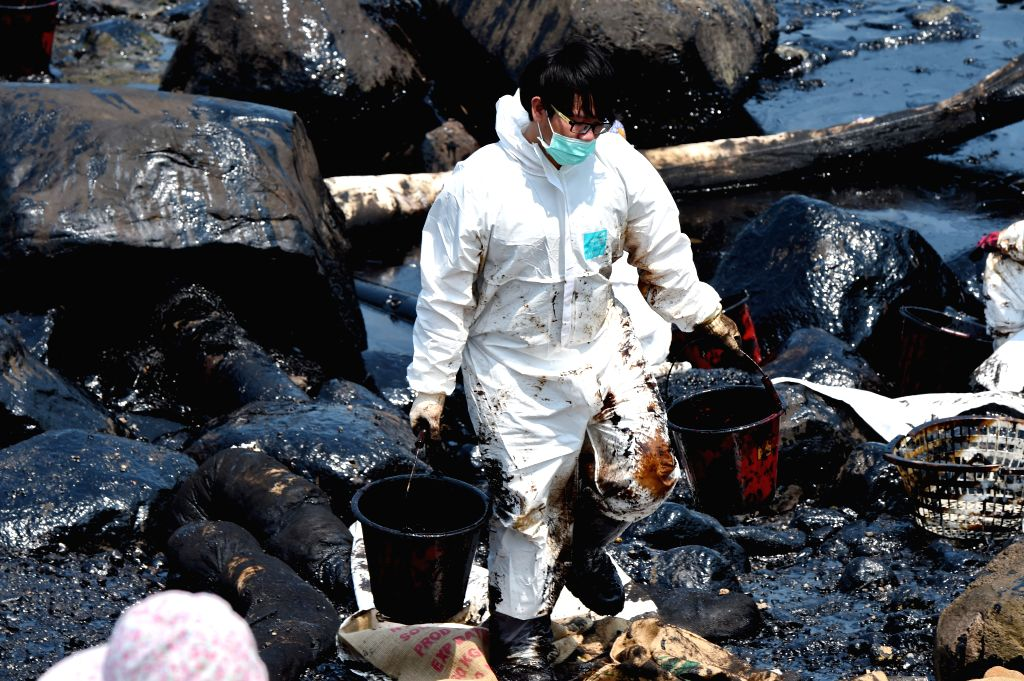 TAIPEI, March 29, 2016 - A worker carries buckets of oil, which leaked from a cargo vessel, on the seaside of New Taipei City, southeast China's Taiwan, March 29, 2016. The stranded vessel carrying ...