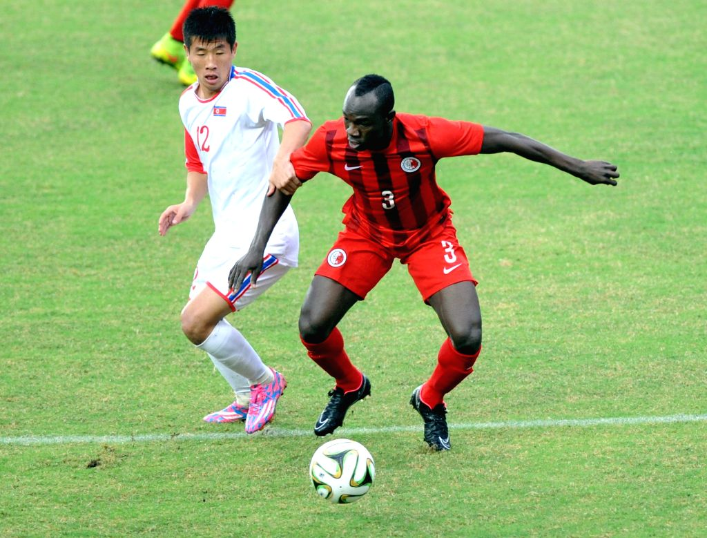 Om Chol Song (L) of the Democratic People's Republic of Korea (DPRK) vies with Agbo Fofo Wisdom of China's Hong Kong during their semifinals round match at the 2015 EAFF East Asian Cup in ...