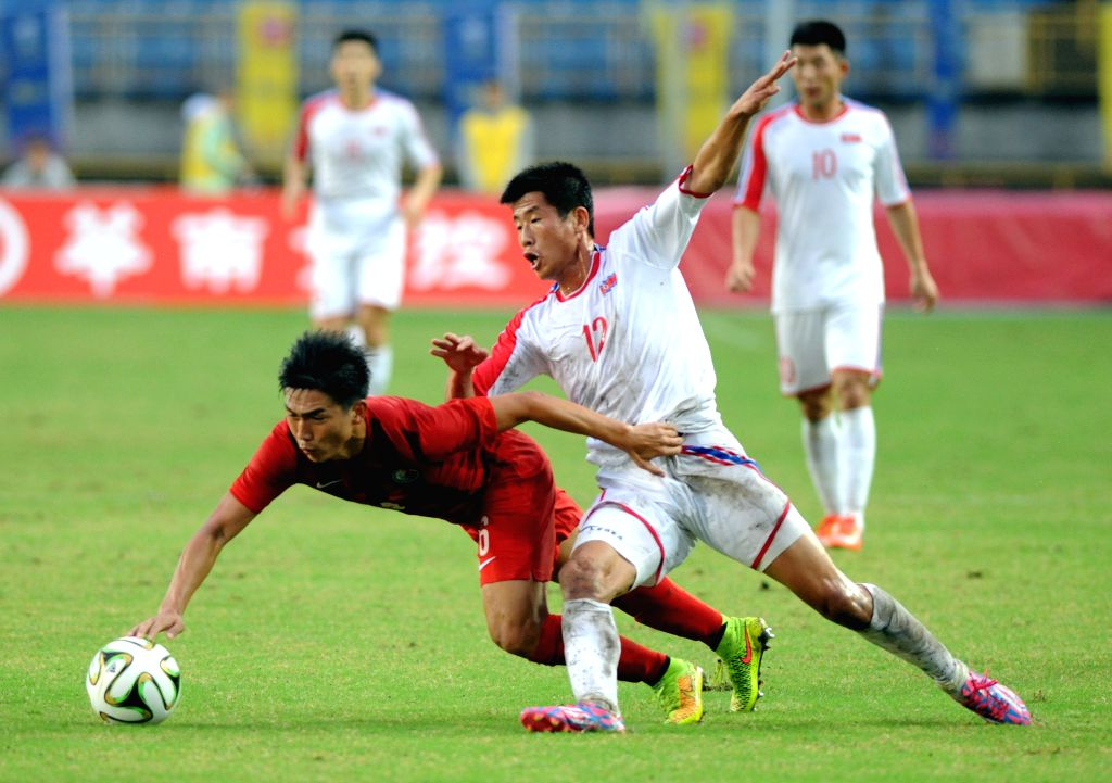 Om Chol Song (R) of the Democratic People's Republic of Korea (DPRK) vies for the ball during the semifinals round match against China's Hong Kong at the 2015 EAFF East Asian Cup in Taipei, ..