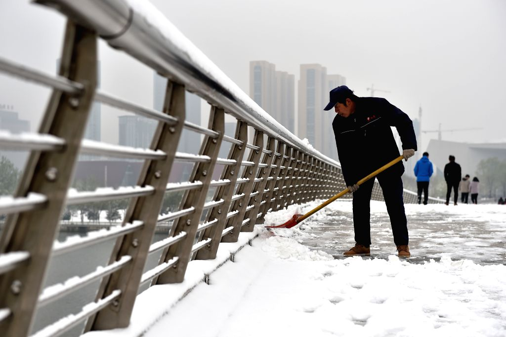 TAIYUAN, April 5, 2018 - A man clears snow on a bridge in Taiyuan, capital of north China's Shanxi Province, April 5, 2018. A cold front brought snowfall to parts of China in these days.
