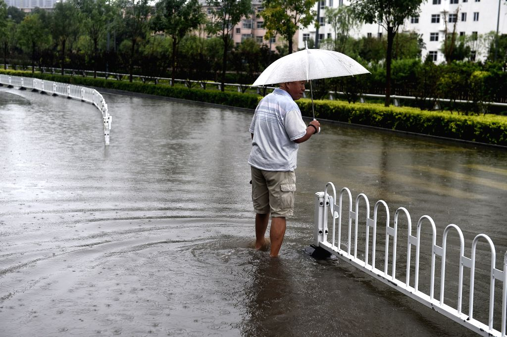 TAIYUAN, July 19, 2016 - A man stands on a flooded street in Taiyuan, capital of north China's Shanxi Province, July 19, 2016. A heavy rain hit Taiyuan on Tuesday. The city's meteorological center ...