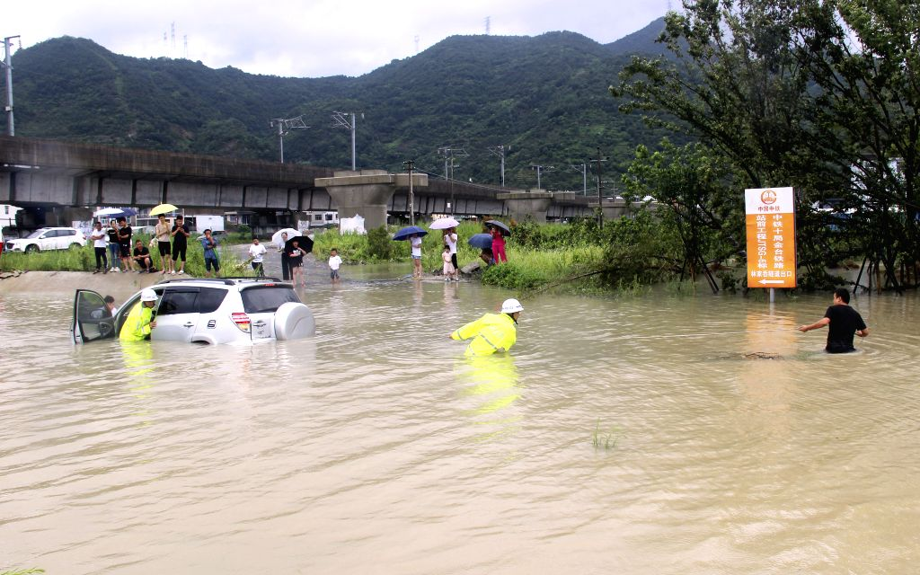 TAIZHOU, Aug. 10, 2019 - Traffic police officers move a flood-stranded car in Luqiao District of Taizhou City, east China's Zhejiang Province, Aug. 10, 2019. Typhoon Lekima, the ninth of the year, ...