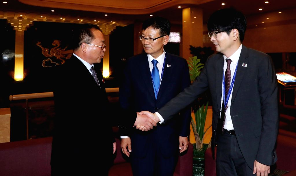 Tak Hyun-min (R), a protocol presidential aide to South Korean President Moon Jae-in, shakes hands with Jon Jong-su, a co-head of the inter-Korean liaison office in the North Korean border ...