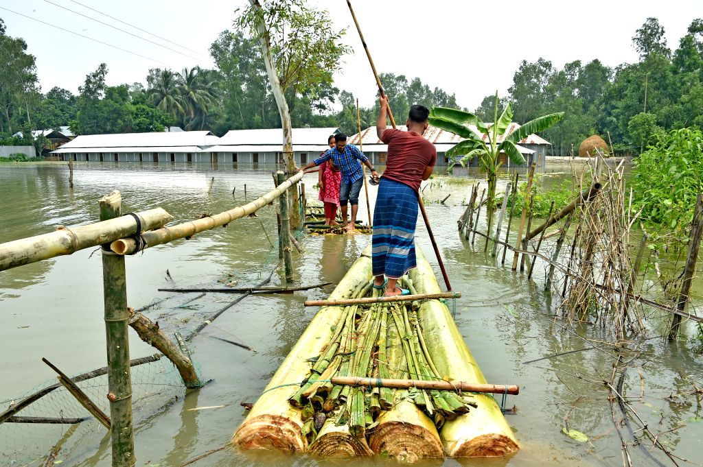 TANGAIL (BANGLADESH), July 18, 2019 People row makeshift rafts through flood waters in Tangail, Bangladesh, on July 18, 2019. Flash floods sparked by heavy seasonal rains affected parts ...