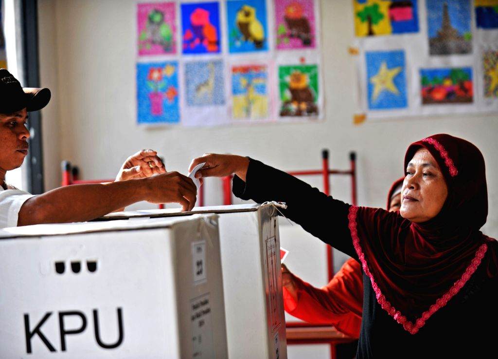 A woman casts her vote at a polling station in Tangerang, Indonesia, July 9, 2014. Indonesians on Wednesday went to polls to pick up their new president for the ...