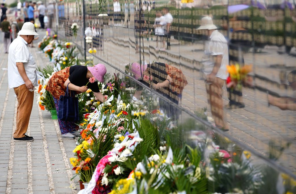 TANGSHAN, July 27, 2018 - People mourn for relatives killed in the 1976 Tangshan earthquake in front of the memorial wall in Tangshan, north China's Hebei Province, July 27, 2018, one day before the ...