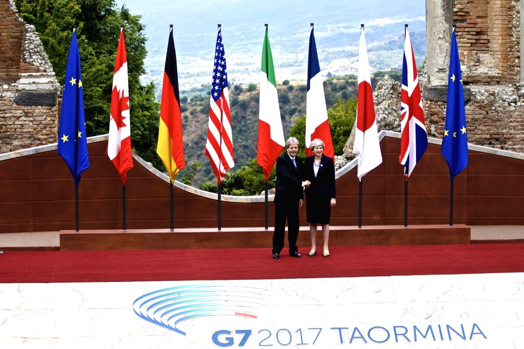 TAORMINA, May 26, 2017 - British Prime Minister Theresa May (R) shakes hands with Italian Prime Minister Paolo Gentiloni at the ancient Greek theatre of Taormina before the opening ceremony of a G7 ... - Theresa May