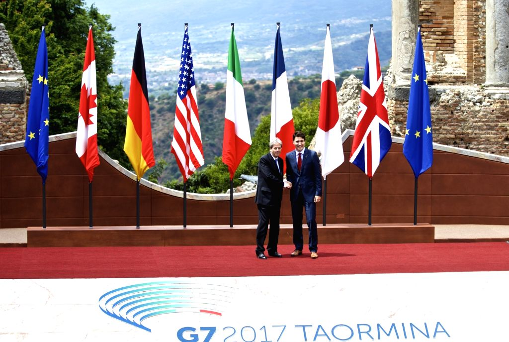 TAORMINA, May 26, 2017 - Canadian Prime Minister Justin Trudeau (R) shakes hands with Italian Prime Minister Paolo Gentiloni at the ancient Greek theatre of Taormina before the opening ceremony of a ... - Justin Trudeau