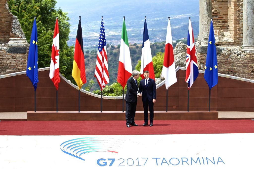 TAORMINA, May 26, 2017 - French President Emmanuel Macron (R) shakes hands with Italian Prime Minister Paolo Gentiloni at the ancient Greek theatre of Taormina before the opening ceremony of a G7 ... - Paolo Gentiloni