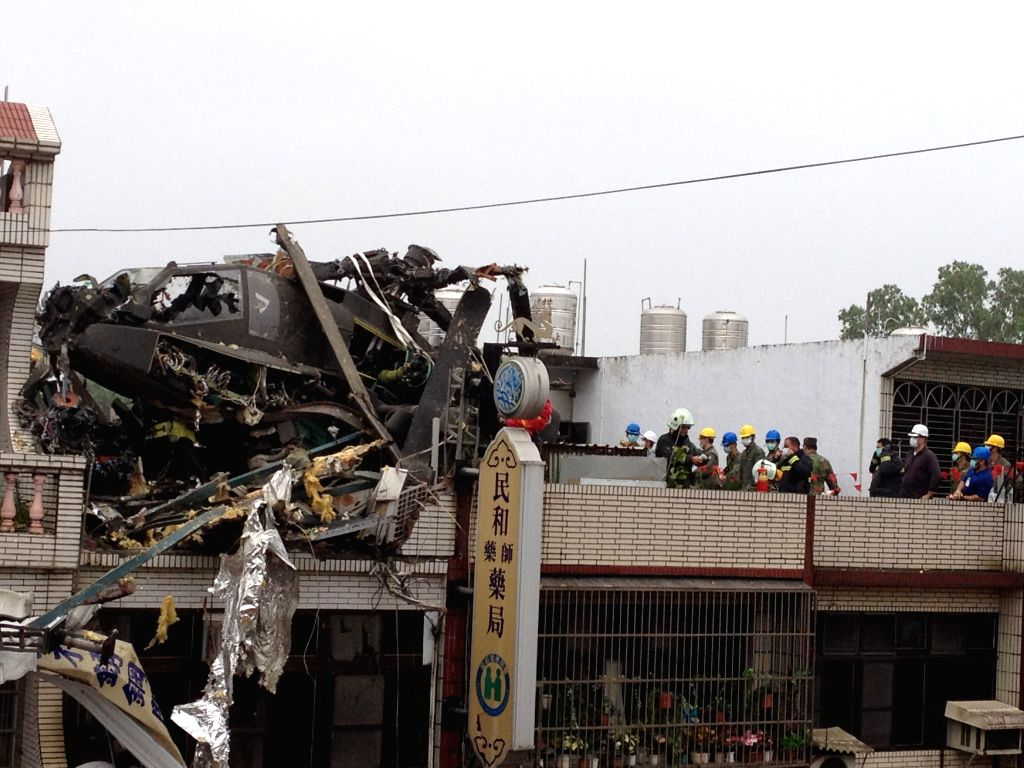 Photo taken with a cellphone on April 25, 2014 shows a military helicopter crashing into a residential builiding in Taoyuan County, southeast China's Taiwan.  The .