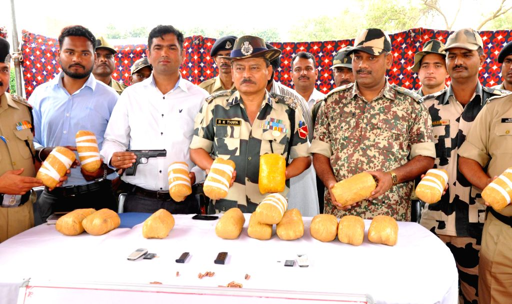 Tarn Taran: Deputy Inspector General of BSF RK Thapa and other officials present before press 20 kilogram heroin, two pistols, 17 live rounds , two mobile phones and two Pak SIM cards recovered by ...
