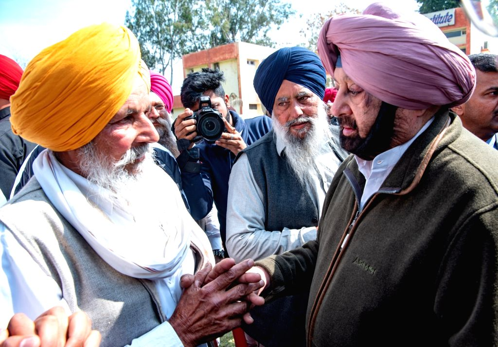 Tarn Taran: Punjab Chief Minister Captain Amarinder Singh meets father of Pulwama martyr Sukhjinder Singh during a tour of border areas in Tarn Taran district as part of his confidence-building measures for residents, on Feb 28, 2019. (Photo: IANS) - Captain Amarinder Singh and Sukhjinder Singh