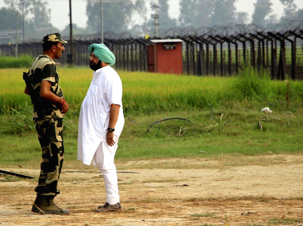 Tarn Taran: Punjab Congress chief Captain Amarinder Singh interacts with BSF personals at the border fence during his tour of border villages in Taran Taran on Oct 4, 2016. - Amarinder Singh