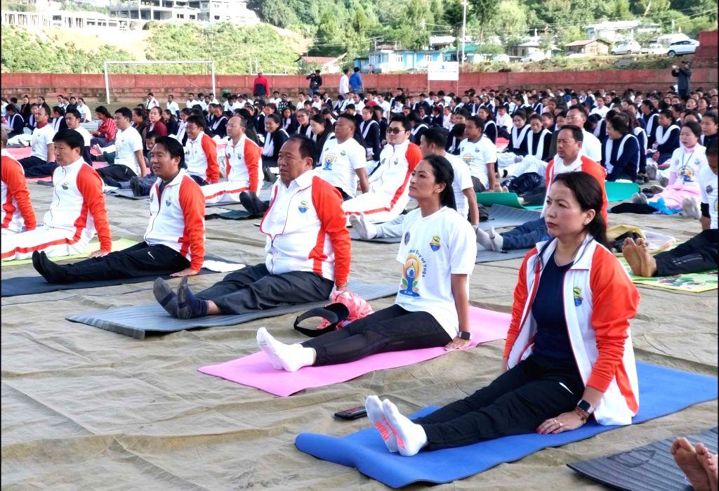 Tawang: People practice yoga asanas - postures - on the 5th International Yoga Day at Gyalwa Tsangyang Gyatso High Altitude Stadium in Tawang, Arunachal Pradesh on June 21, 2019. (Photo: IANS)