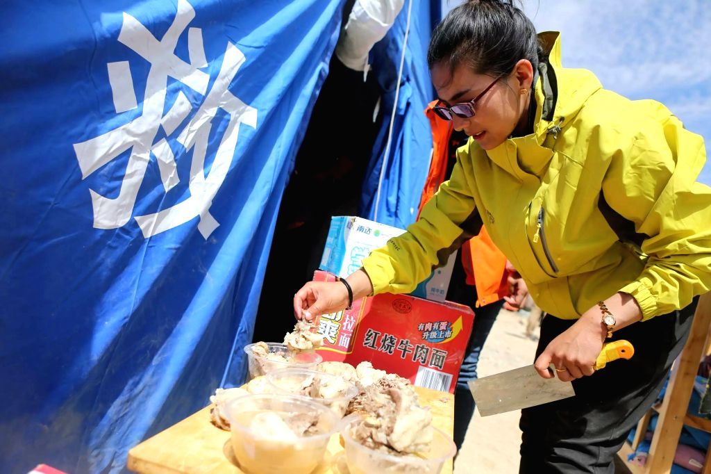 TAXKORGAN, May 13, 2017 - A volunteer prepares mutton for children at a temporary kindergarten of an emergency shelter in Quzgun Village of quake-hit Taxkorgan County, northwest China's Xinjiang ...