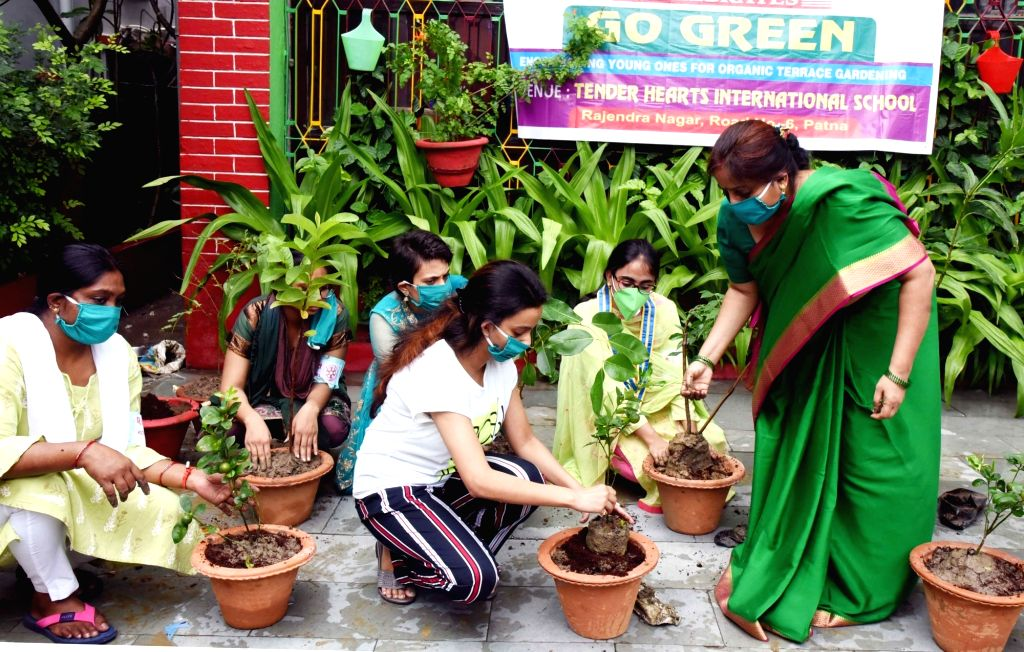 "Teachers and staff of a school participate in a plantation drive as part of the ""Go Green"" campaign organised during Sawan Milan programme, in Patna on July 6, 2020."