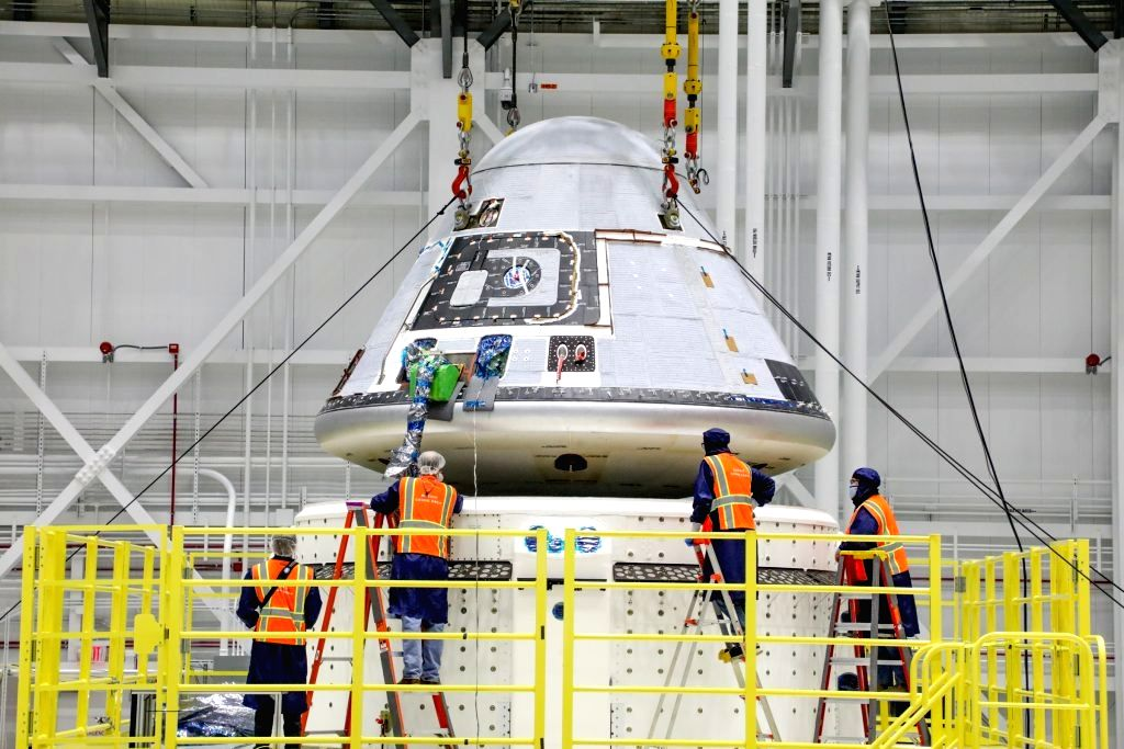 Technicians observe Boeing???s Starliner crew module being placed on top of the service module in the Commercial Crew and Cargo Processing Facility at NASA???s Kennedy Space Center in Florida on ...