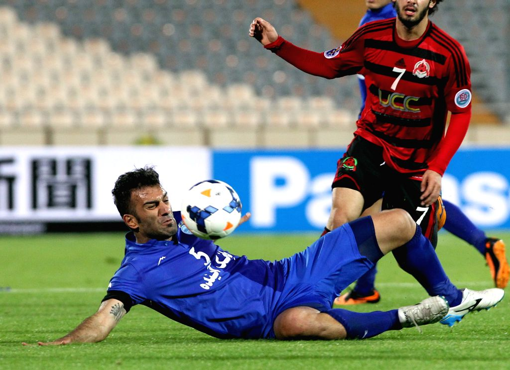 Hanif Omranzadeh (L) of Iran's Esteghlal vies for the ball against Qatar's Al-Rayyan during the AFC Champions League Group A preliminary match in Tehran, Iran, on ..