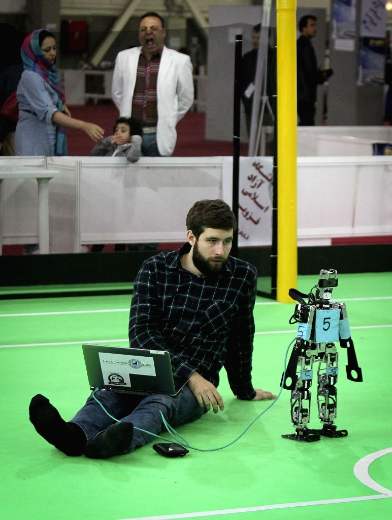 A German student adjusts his robot before a football match during the 9th RoboCup Iran Open 2014 Competitions in Tehran, capital of Iran, on April 9, 2011. More than