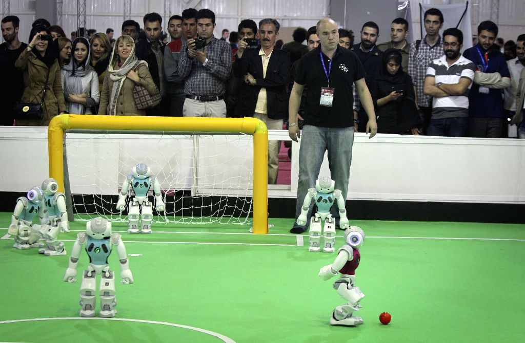 Robots made by German and Holland contestants play football during the 9th RoboCup Iran Open 2014 Competitions in Tehran, capital of Iran, on April 9, 2011. More ...