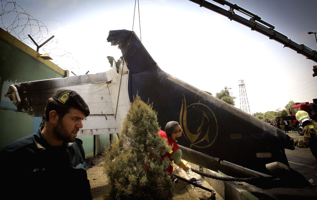 An Iranian soldier looks at the wreckage of a plane which crashed near Tehran, Iran on Aug. 10, 2014. A passenger plane crashed on the outskirts of Iran's capital ...