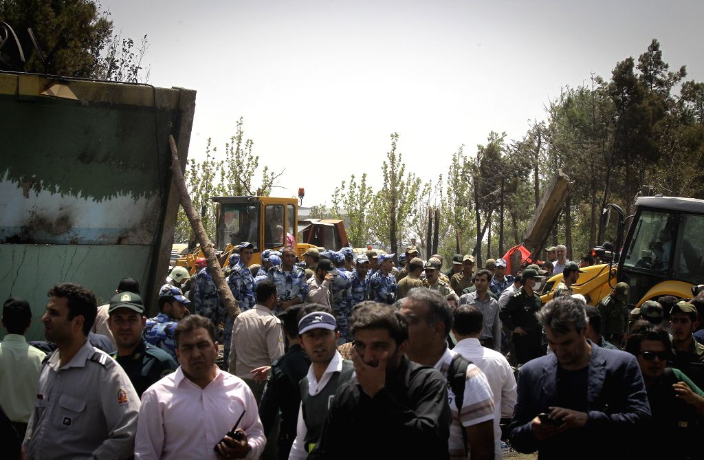 Iranian soldiers and security guards stand around the wreckage of a plane which crashed near Tehran, Iran on Aug. 10, 2014. A passenger plane crashed on the ...