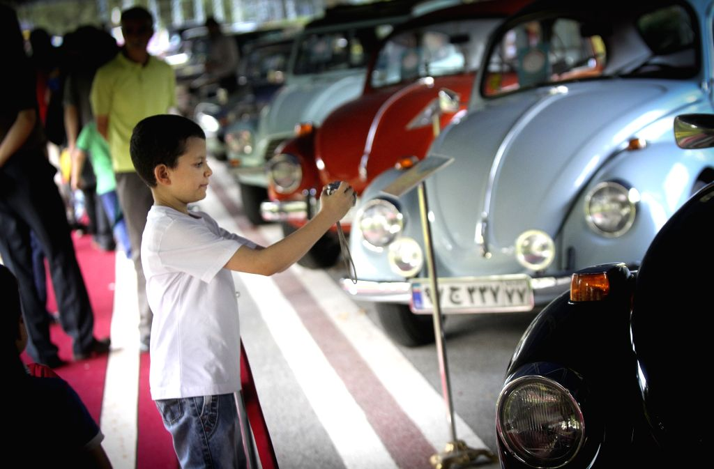 An Iranian boy takes photos during a classic car exhibition in Tehran, Iran, on Aug. 8, 2014. More than 70 classic cars are displayed during the six-day-long ...