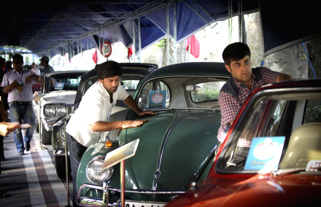 Two men clean cars during a classic car exhibition in Tehran, Iran, on Aug. 8, 2014. More than 70 classic cars are displayed during the six-day-long exhibition. ...