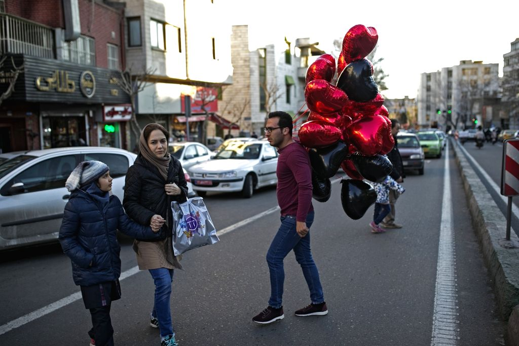 TEHRAN, Feb. 14, 2018 - A man carries balloons for his customers on a street on Valentine's Day in Tehran, capital of Iran, on Feb. 14, 2018.