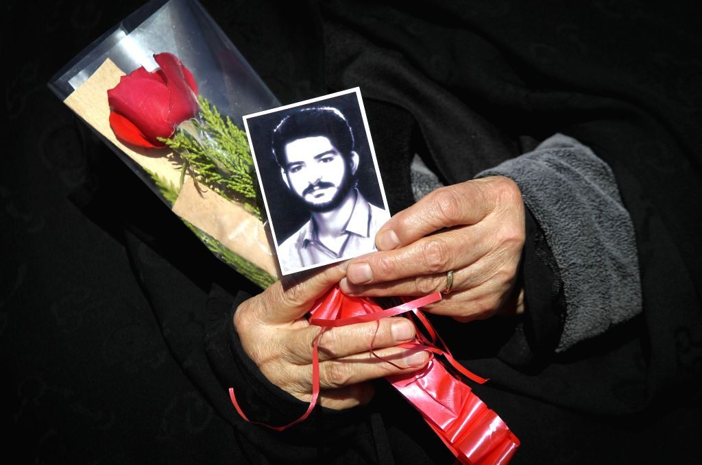 An Iranian woman holds a picture of her son who was killed during the 1979 Islamic revolution at the Behesht-e Zahra cemetery outside Tehran, Iran, on Feb. 1, 2015, ..