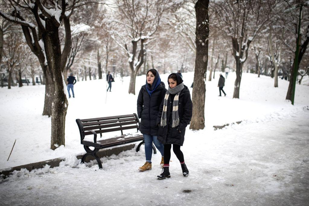 TEHRAN, Jan. 31, 2018 - Women walk in a park after a snowfall in Tehran, capital of Iran, on Jan. 30, 2018.