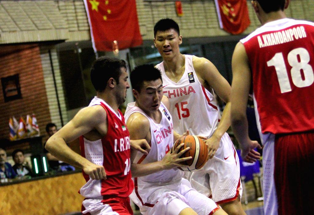 TEHRAN, July 29, 2016 - Jie Tang (C, front) of China drives the ball during a match between China and Iran at 24th Fiba Asia U18 Championship in Tehran, Iran, on July 29, 2016. Iran won the match ...