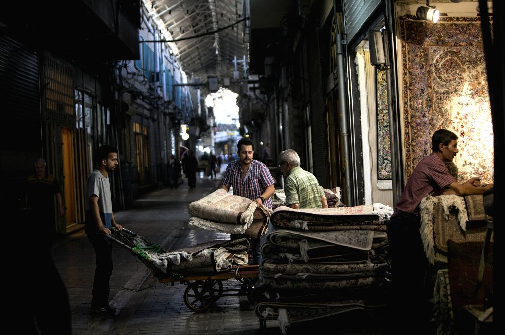 TEHRAN, July 30, 2018 - Workers carry handwoven carpets at a bazaar in downtown Tehran, Iran, on July 30, 2018. Iran will file a lawsuit with international tribunals against U.S. fresh sanctions on ...