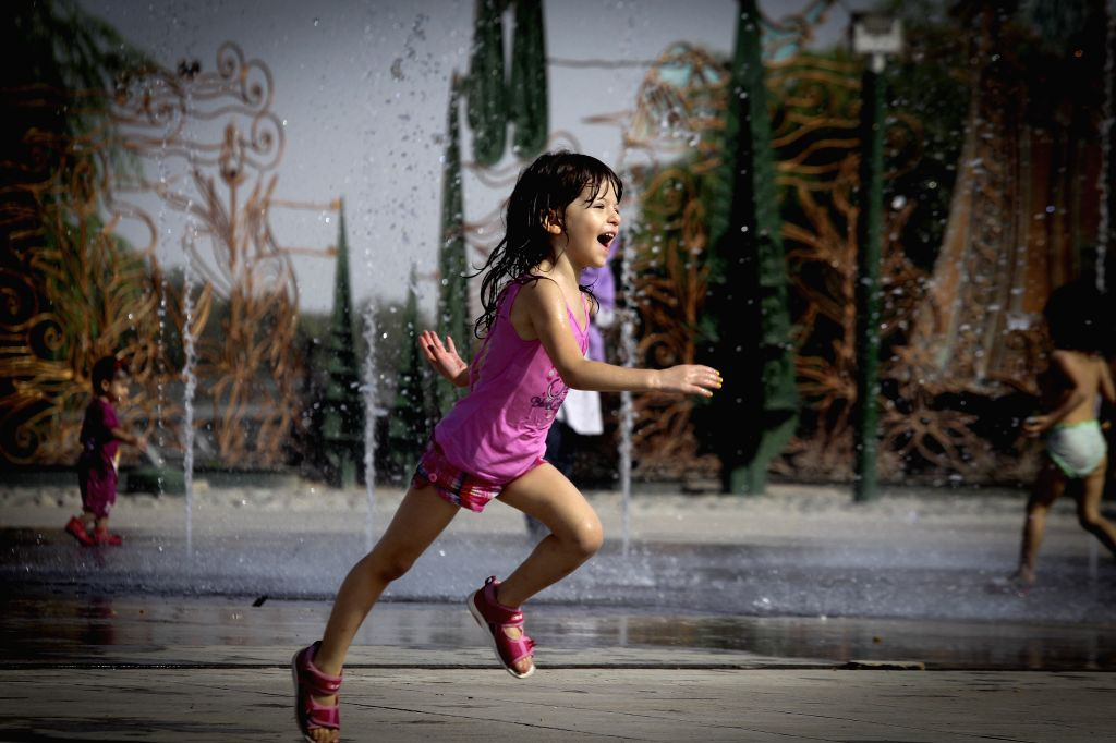 An Iranian girl runs at a park in Tehran, Iran, on July 30, 2014. A heatwave with the temperature of over 40 degrees Celsius swept the city in the past days. ...