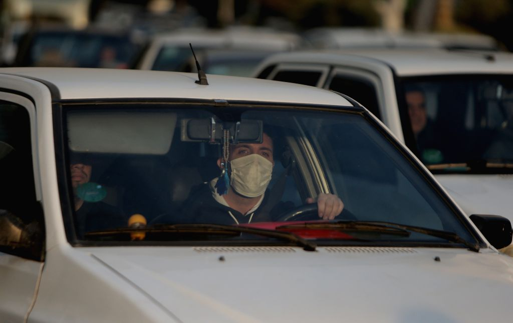 TEHRAN, Nov. 15, 2019 - A man wearing a mask drives his car in Tehran, Iran, on Nov. 14, 2019. The Iranian authorities closed kindergartens and primary schools on Wednesday over serious air pollution ...