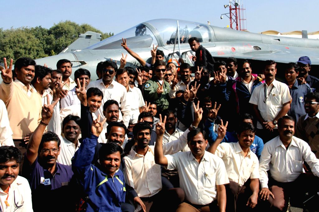 `Tejas` team pose for a photograph with indigenously-designed `Tejas`, regarded as the smallest and the lightest combat jet in the world, after it passed initial operational clearance (IOC-II) test ..