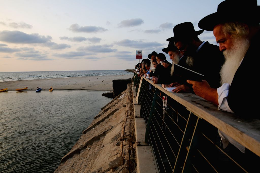 TEL AVIV (ISRAEL), Oct. 10, 2016 Ultra-Orthodox Jews pray as they take part in Tashlich on the shore of the Mediterranean Sea in Tel Aviv, Israel, Oct. 9, 2016. Tashlich is a ritual ...