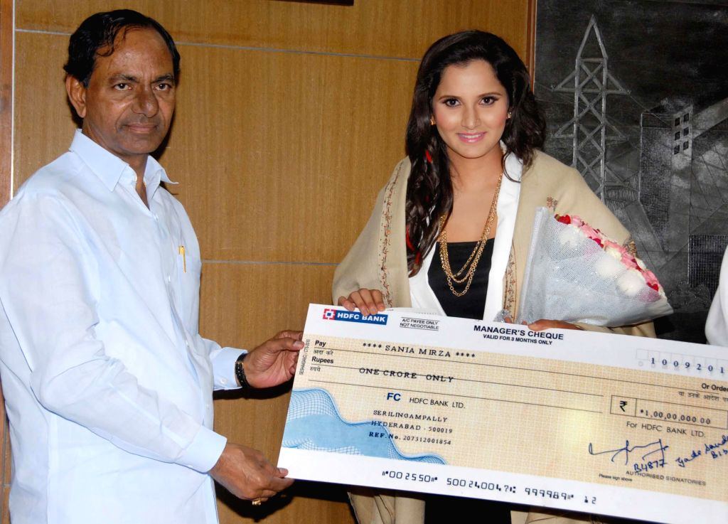 Telangana Chief Minister K Chandrasekhar Rao presents a cheque of Rs. 1 crore to Indian tennis player Sania Mirza in Hyderabad on Sept 11, 2014. - K Chandrasekhar Rao