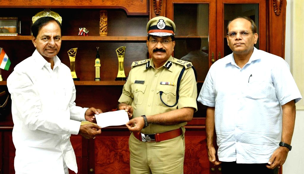 Telangana Director General of Police (DGP) M. Mahender Reddy hands over a cheque to Chief Minister K. Chandrashekar Rao, donating his one month's salary to the Chief Minister's Fund during ... - K. Chandrashekar Rao and M. Mahender Reddy