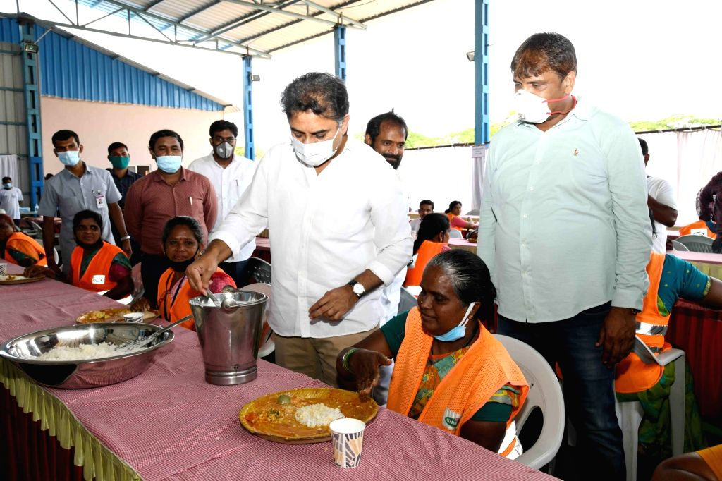 Telangana Municipal Administration and Urban Development Minister KT Rama Rao serves rice to a sanitation worker in Hyderabad during the extended nationwide lockdown imposed to mitigate ... - K and Rao