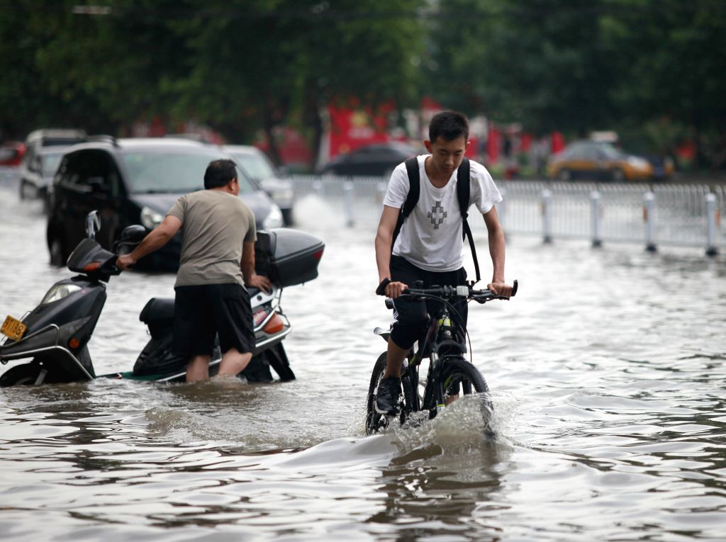 TENGZHOU, Aug. 2, 2016 - Residents ride on a waterlogged street in Tengzhou City, east China's Shandong Province, Aug. 2, 2016. Tengzhou meteorological authorities have issued red alert for rain, the ...