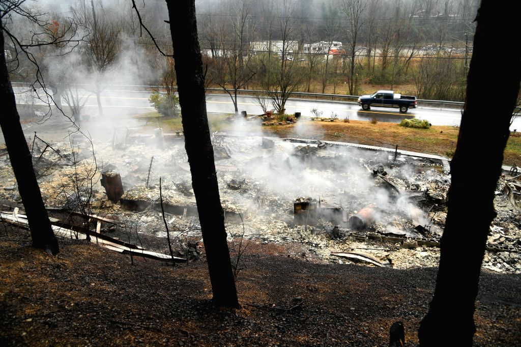TENNESSEE (U.S.), Nov. 30, 2016 A car runs past the debris of a house which was ruined by a wildfire in Pigeon Forge, Sevier County, Tennessee, the United States, on Nov. 30, 2016. A ...